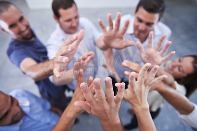 Buy stock photo Shot of a group of coworkers raising their hands together