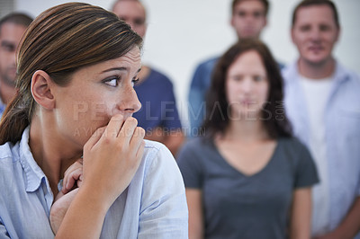 Buy stock photo Shot of a young woman looking nervous in front of her coworkers