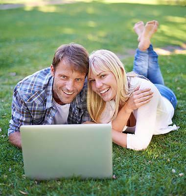 Buy stock photo Portrait of an attractive couple using a laptop outdoors