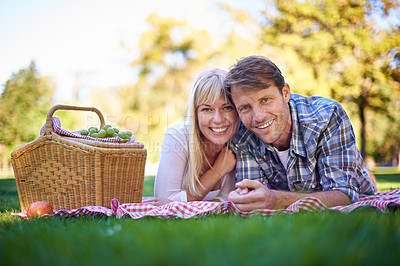 Buy stock photo Shot of an affectionate couple enjoying a picnic in the sun