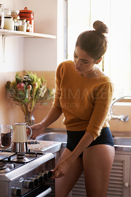 Buy stock photo A young woman using her gas stove to boil water in a kettle
