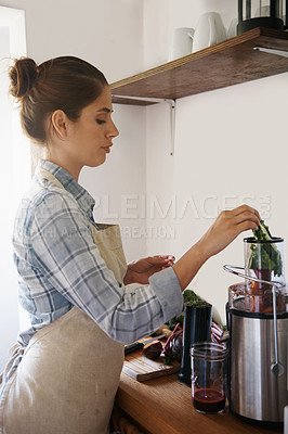 Buy stock photo A woman standing in a kitchen making fresh juice with a juicer