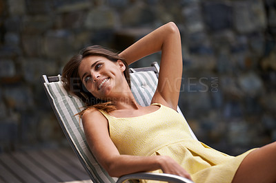 Buy stock photo Shot of a young woman relaxing outdoors while on vacation