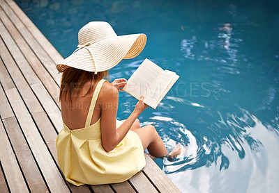 Buy stock photo young woman relaxing at the pool with a book