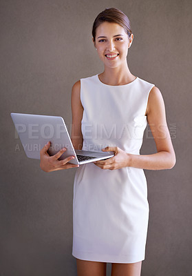 Buy stock photo A pretty young businesswoman holding a laptop while isolated on a white background