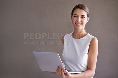 Buy stock photo Portrait of a pretty young businesswoman holding a laptop on a white background
