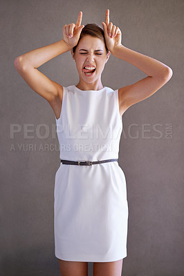 Buy stock photo Expressive young woman using her hands to make horns