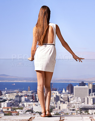 Buy stock photo Rear view of a young woman standing on a balcony while watching the view