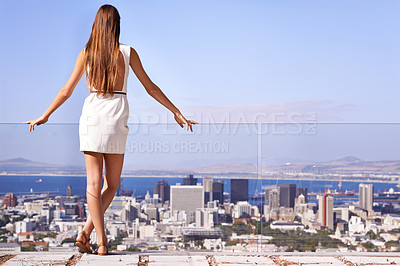 Buy stock photo Rearview shot of a gorgeous young woman overlooking the city
