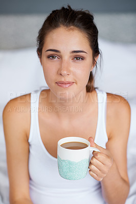 Buy stock photo Shot of a young woman holding a cup of coffee while sitting up in bed