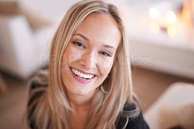 Buy stock photo Portrait of a smiling young woman relaxing at home
