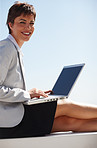 Beautiful business woman working on a laptop while sitting outdoors