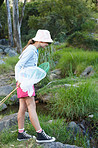Portrait of a cute young girl fishing by a stream