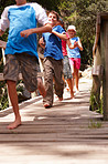 Group of happy young children running on a wooden bridge, outdoors