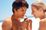 Happy young couple at the beach having a treat