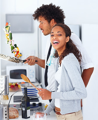 Happy young couple preparing food together at home