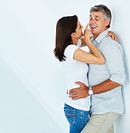 Happy mature couple in a playful mood fondling eachother over a white background