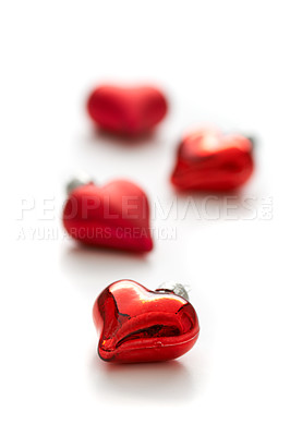 Buy stock photo Closeup of heart-shaped christmas decorations scatterd on a white background - copyspace