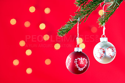 Buy stock photo Christmas baubles hanging from a tree branch, isolated on red with scattered light effect - copyspace