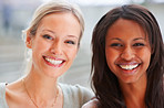 An African American woman with her blond friend smiling