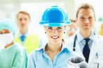 Beautiful young female architect in blue cap smiling with people standing behind