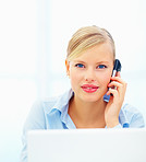 Businesswoman sitting in front of laptop talking on mobile phone