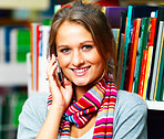 Closeup of a beautiful lady using cellphone with books on background