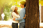 Couple standing against a tree and hugging