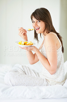 Buy stock photo Happy young woman eating fruit salad at home