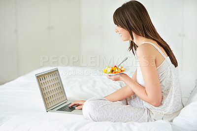 Buy stock photo Young female using laptop and eating fruit salad