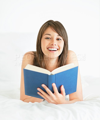 Buy stock photo Young lady reading a book while lying on bed