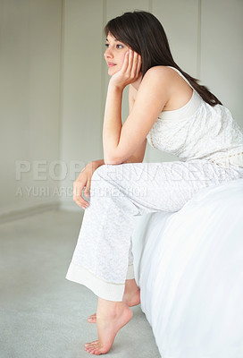 Buy stock photo Daydreaming - Young woman sitting on bed