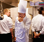 Tired chef with colleagues in kitchen