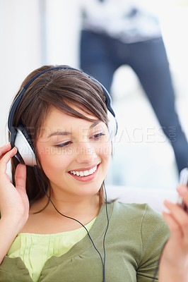 Buy stock photo Pretty teenaged female hearing  music on mp3