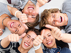 Happy young friends lying down showing thumbs up sign