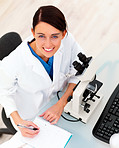Female researcher with microscope and writing notes
