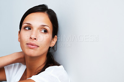 Buy stock photo Pretty woman sitting against the wall thinking