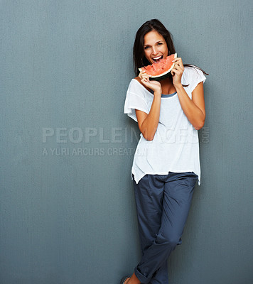 Buy stock photo Woman leaning against blue background holding watermelon up to mouth