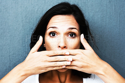 Buy stock photo Woman with both hands in front of mouth against blue background