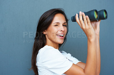 Buy stock photo Side view of pretty woman holding binoculars against blue background