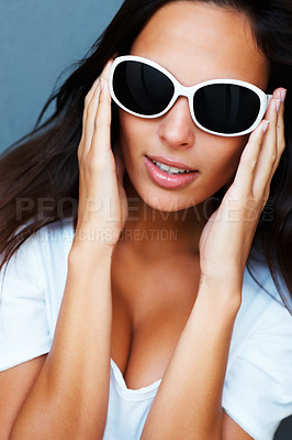 Buy stock photo Pretty woman holding sunglasses on her head against blue background