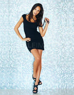 Buy stock photo Woman holding beads with hand on hip against a tiled background