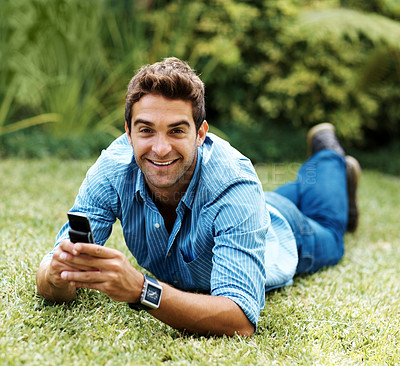Buy stock photo Portrait of a happy young man lying on the grass while talking on the phone