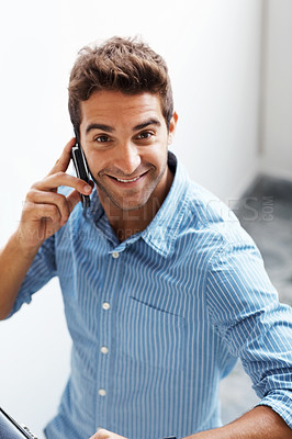 Buy stock photo Portrait of a happy young man speaking on a cellphone