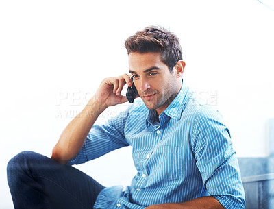 Buy stock photo Shot of a relaxed young man speaking on mobile phone