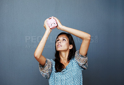 Buy stock photo Portrait of a cute young woman checking her piggy bank for money - Copyspace