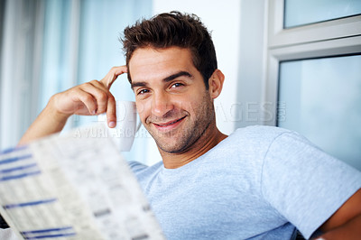 Buy stock photo Portrait of a young man drinkng coffee while reading the newspaper