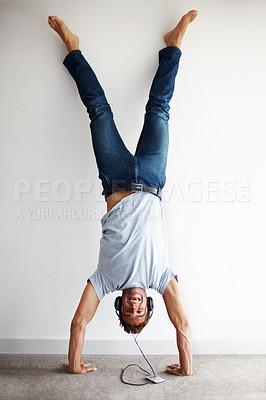 Buy stock photo Shot of an excited young man doing a handstand while listening to music on headphones