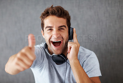 Buy stock photo Portrait of an young man gesturing approval sign to the sound quality of new headphone