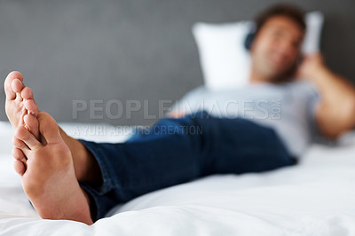 Buy stock photo Portrait of a feet of a young man relaxing on bed while listening to music - Indoor